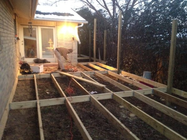 This view shows the deck substructure wrapping around the patio door and the side of the house. The area to the right was too small for even a lawnmower and was never used before the deck.