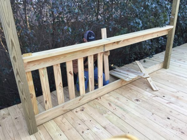 We hand-built the railing around the deck. Since the deck covered two levels of yard, it was about a 4' drop off the end of the deck so we wanted a railing so the kids wouldn't ride their bikes and fall over the edge.
